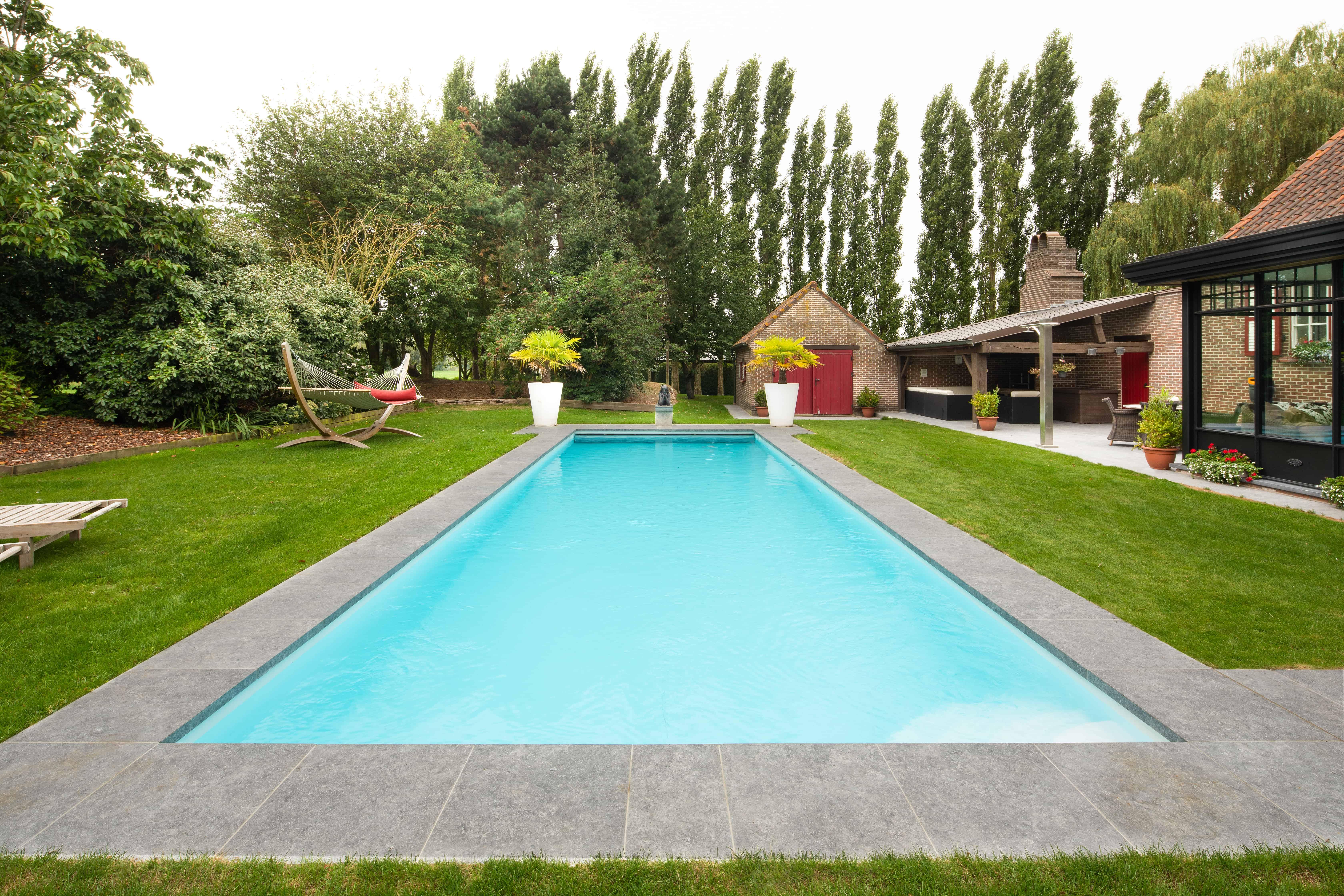 XXL tegels naast zwembad - grote tegels aan zwembad - natuursteen - blauwe hardsteen