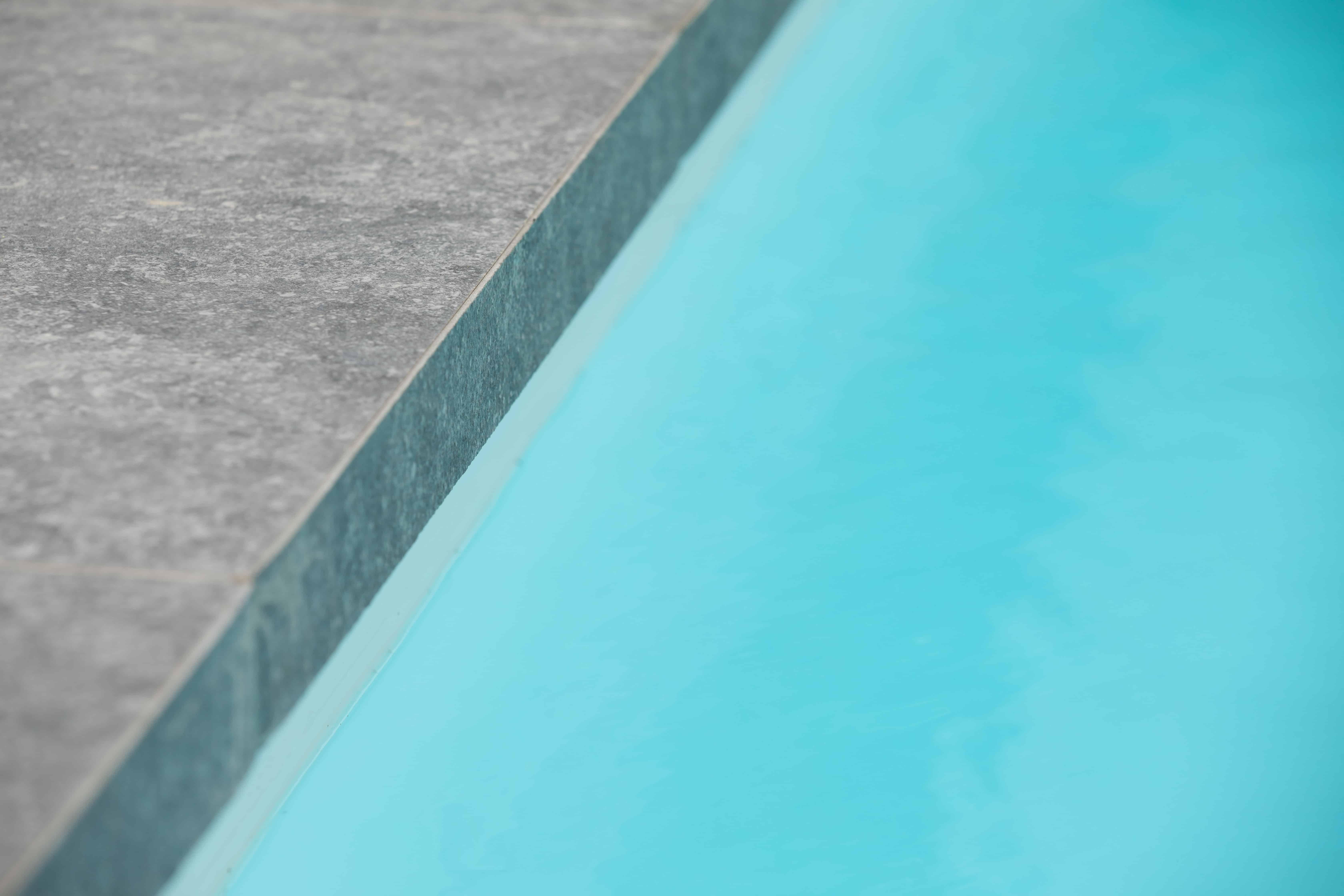tegels aande rand van het zwembad - Natuursteen voor afwerking van zwembad