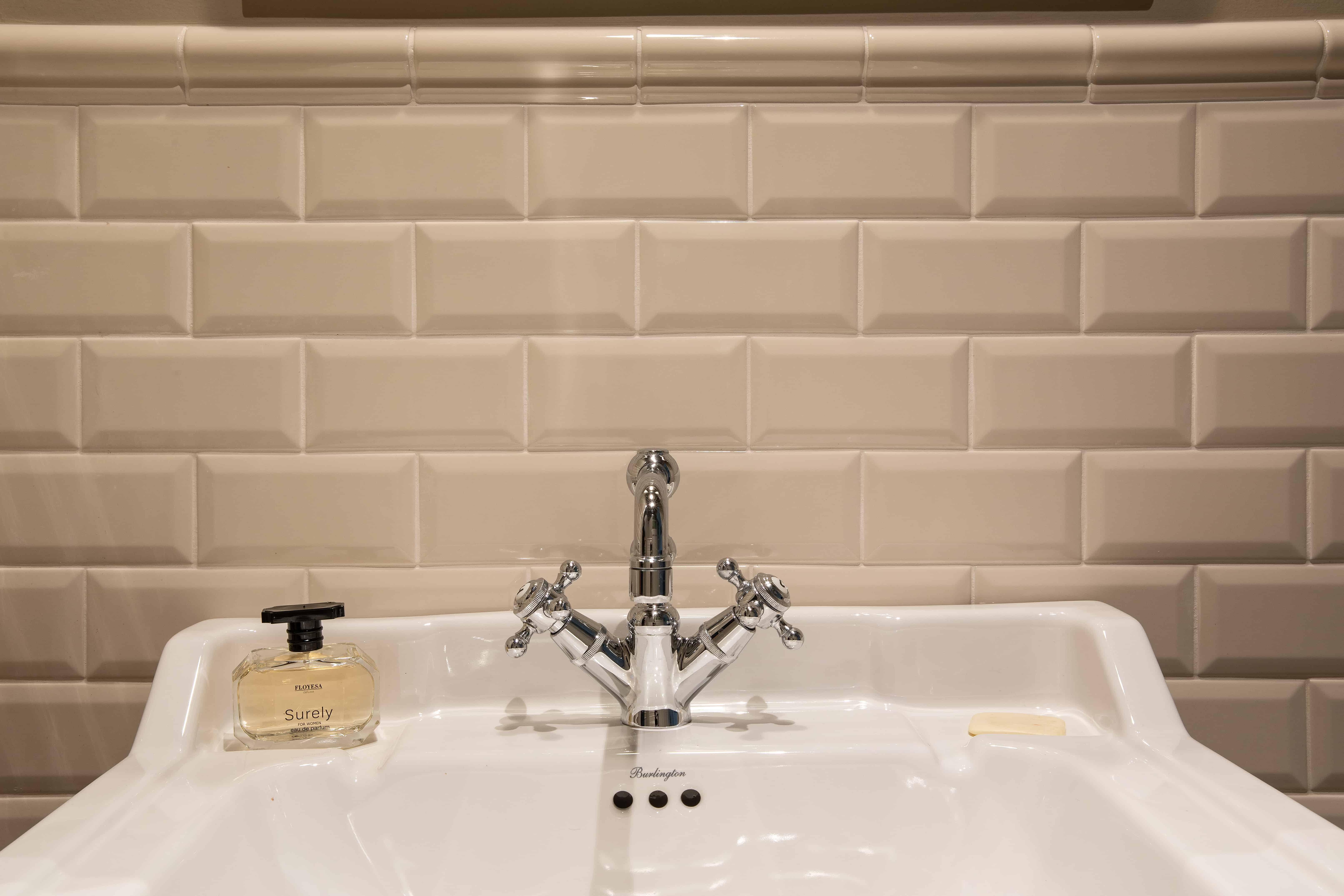 Afwerking badkamer met kleine wandtegels in gebroken wit