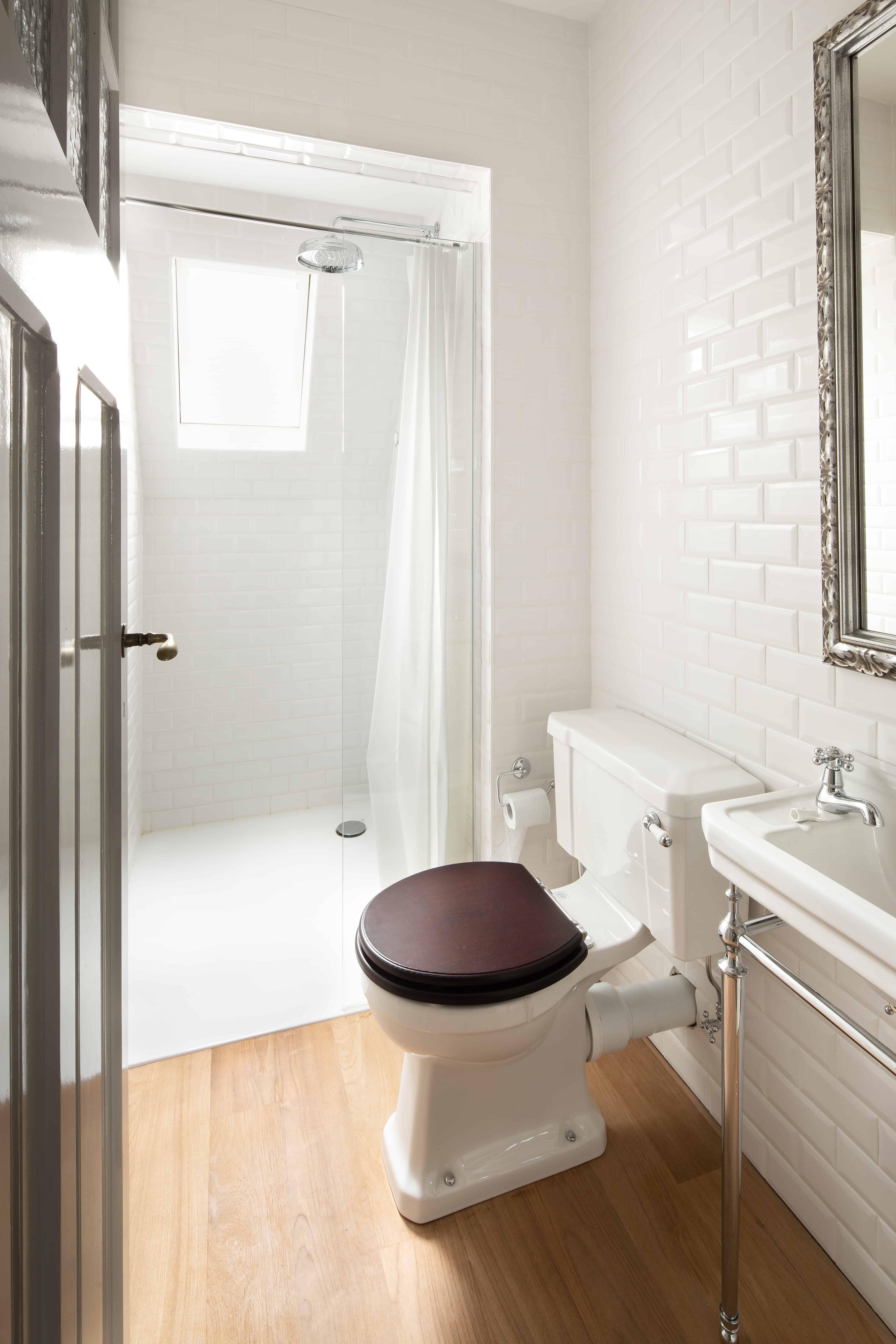 Badkamer met houten vloer en kleine witte wandtegels en XXL tegels in douche - Roeselare