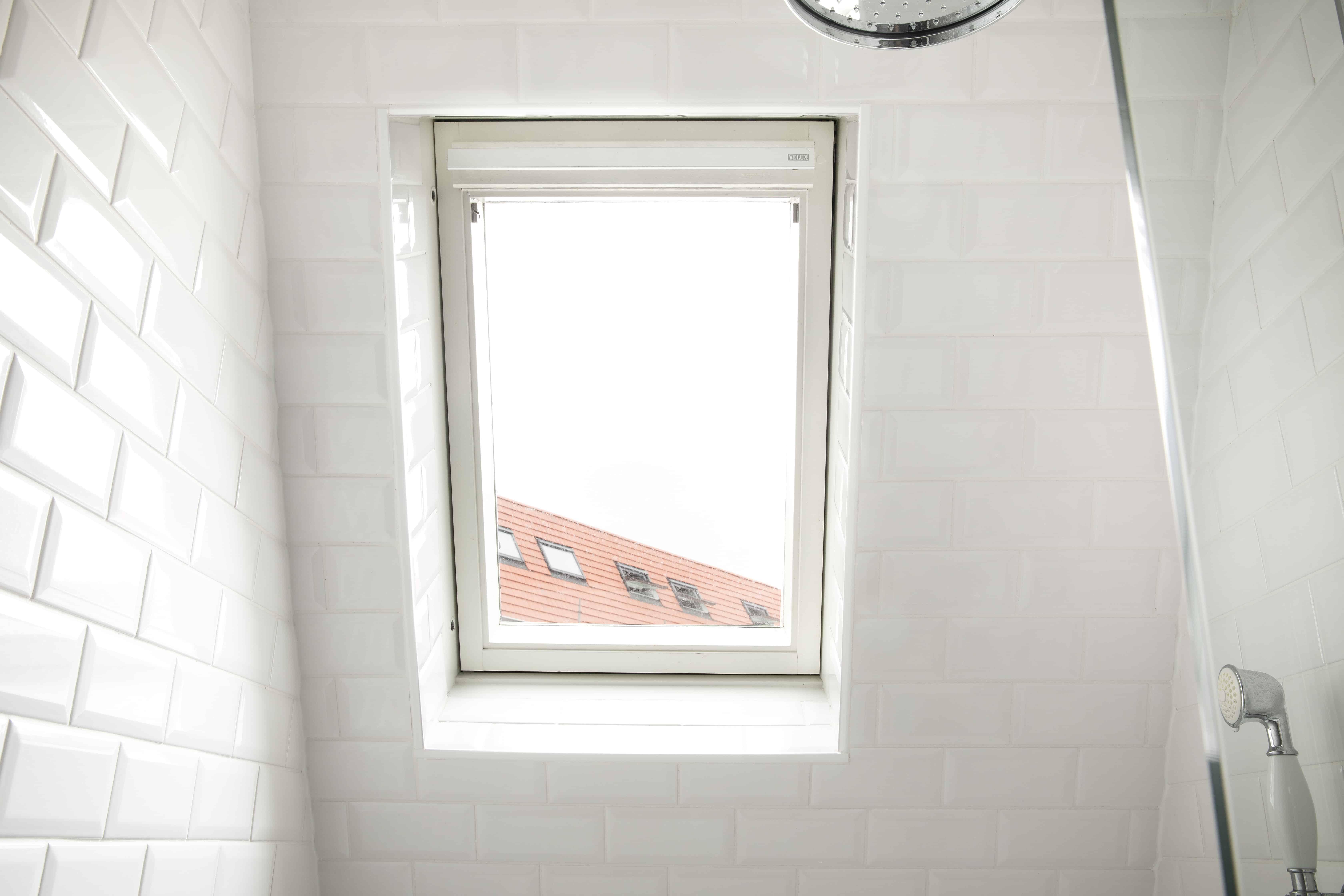 Hellend dak met tegels en velux - wandtegels in hellend dak - witte tegels op hellend dak