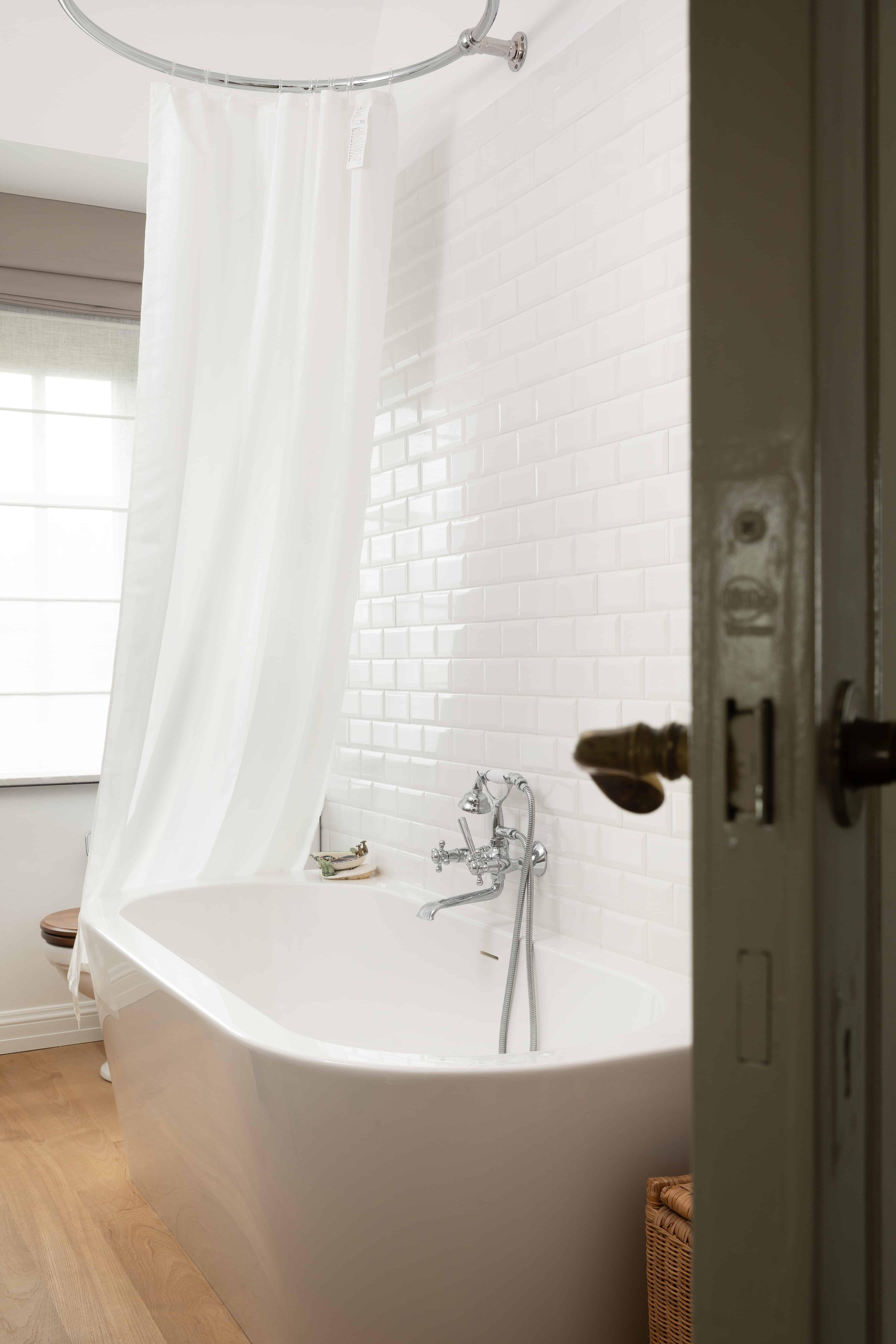 Warme badkamer/ douche / bad met houten vloer en glanzen witte tegels - West-Vlaanderen