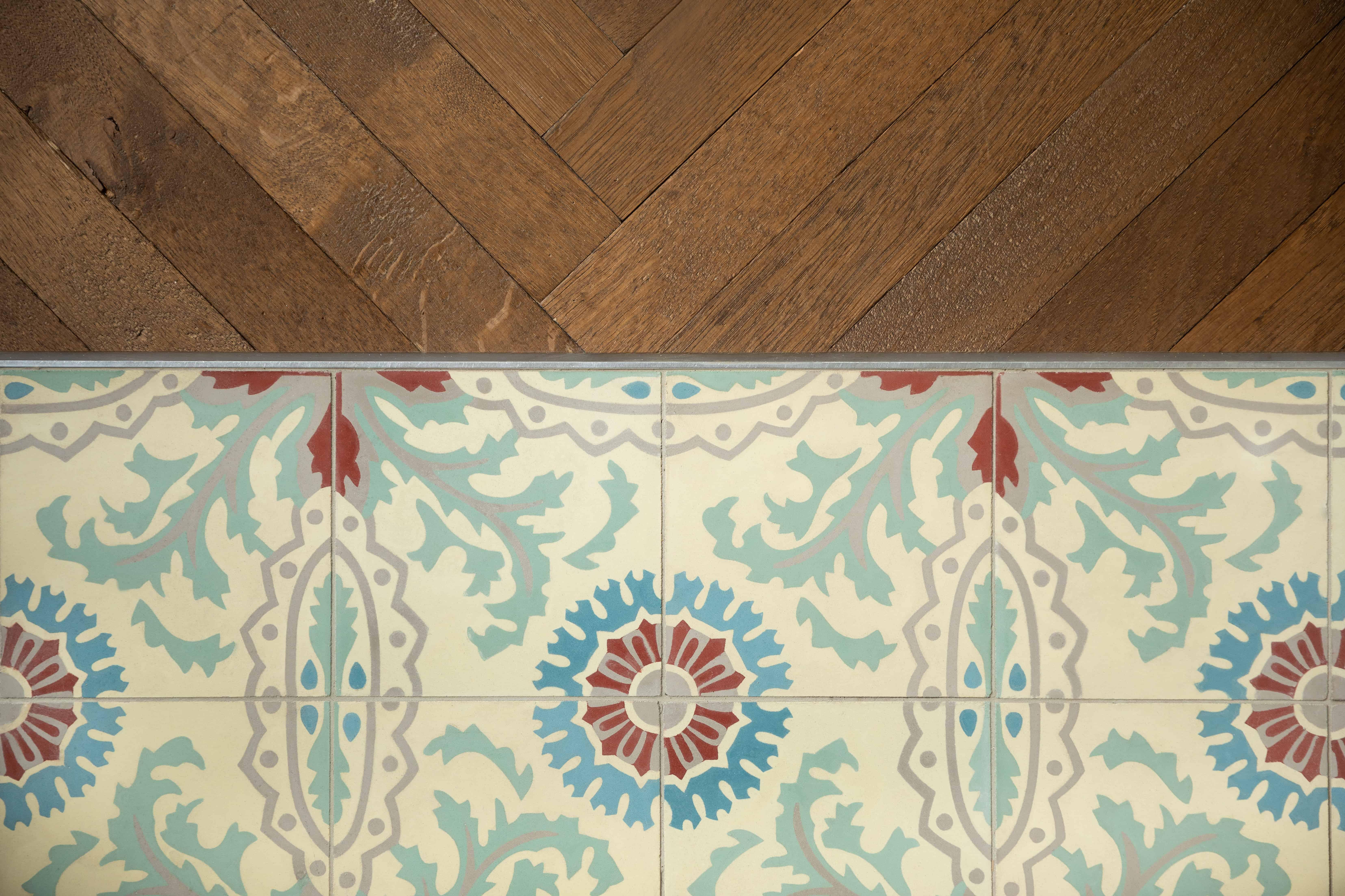 Tegels met origineel retro motief - kleine klassieke tegels naast houten vloer - Gistel